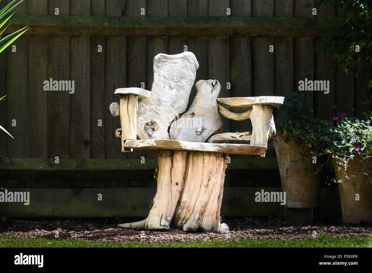Crafted wood bench in front of a fence an a sunny day during summer time in an english garden. - Stock Image