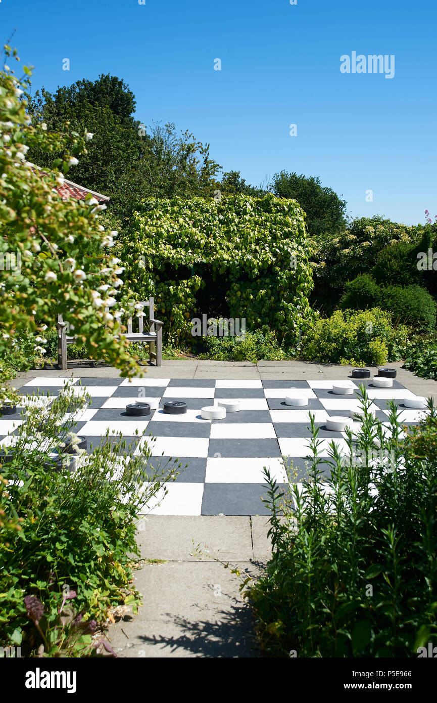 Outdoor giant draughts or checkers game in formal flower garden, Burton Agnes Hall, East Riding of Yorkshire, England, UK, GB - Stock Image