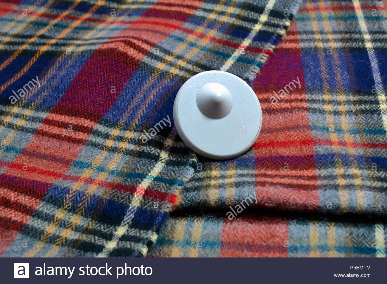 A plastic anti theft security tag on a tartan scarf to stop shoplifting from retail shops - Stock Image