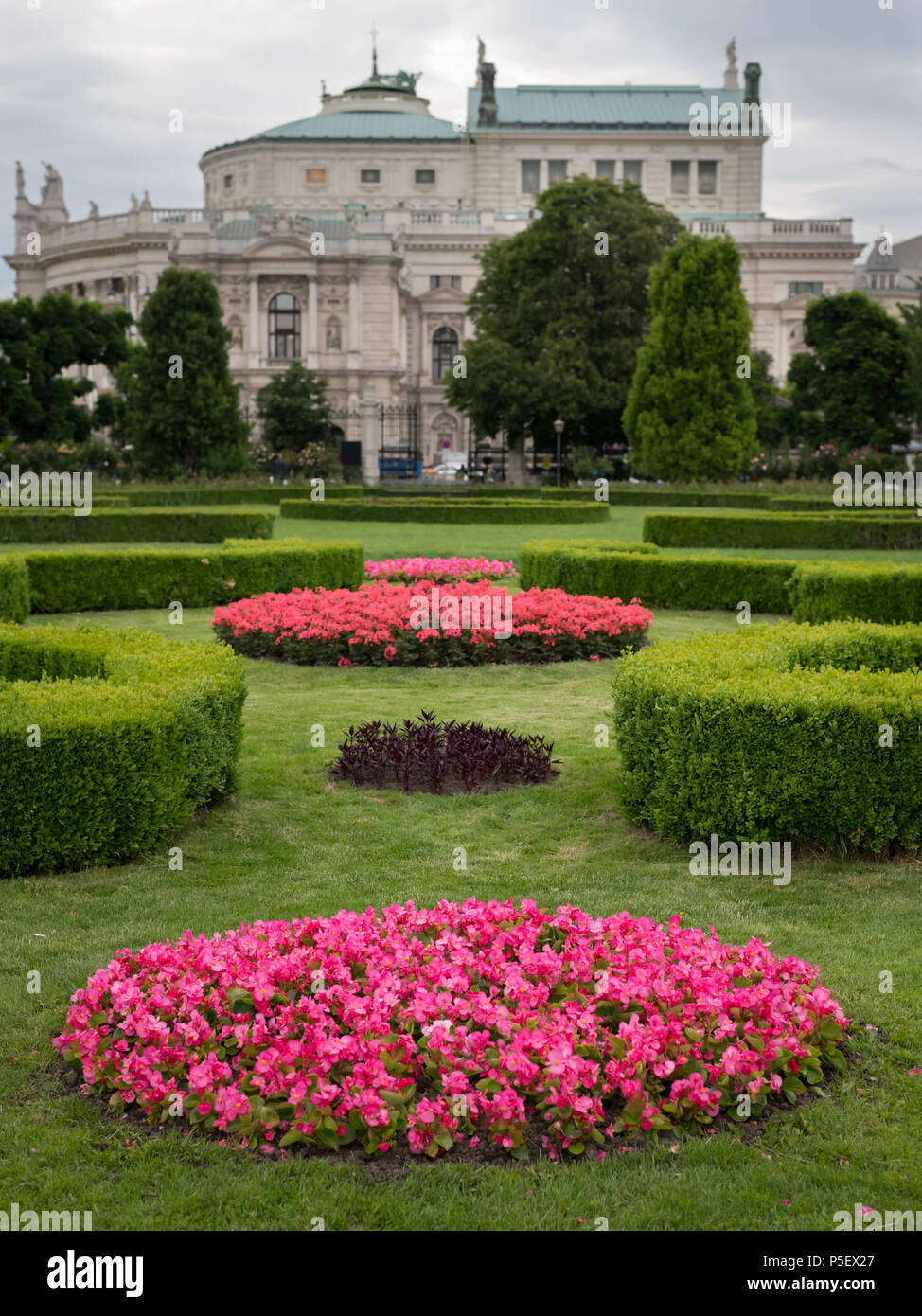 Flowerbed with various flowers, hedges and green meadow in Volksgarten, Vienna (Austria), Court Theatre in the background - Stock Image