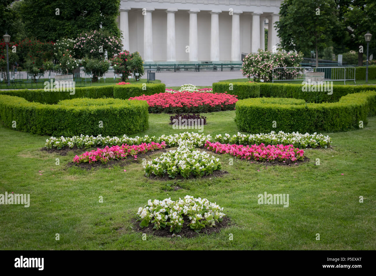 Flowerbed with various flowers, hedges and green meadow in Volksgarten, Vienna (Austria), temple in background Stock Photo