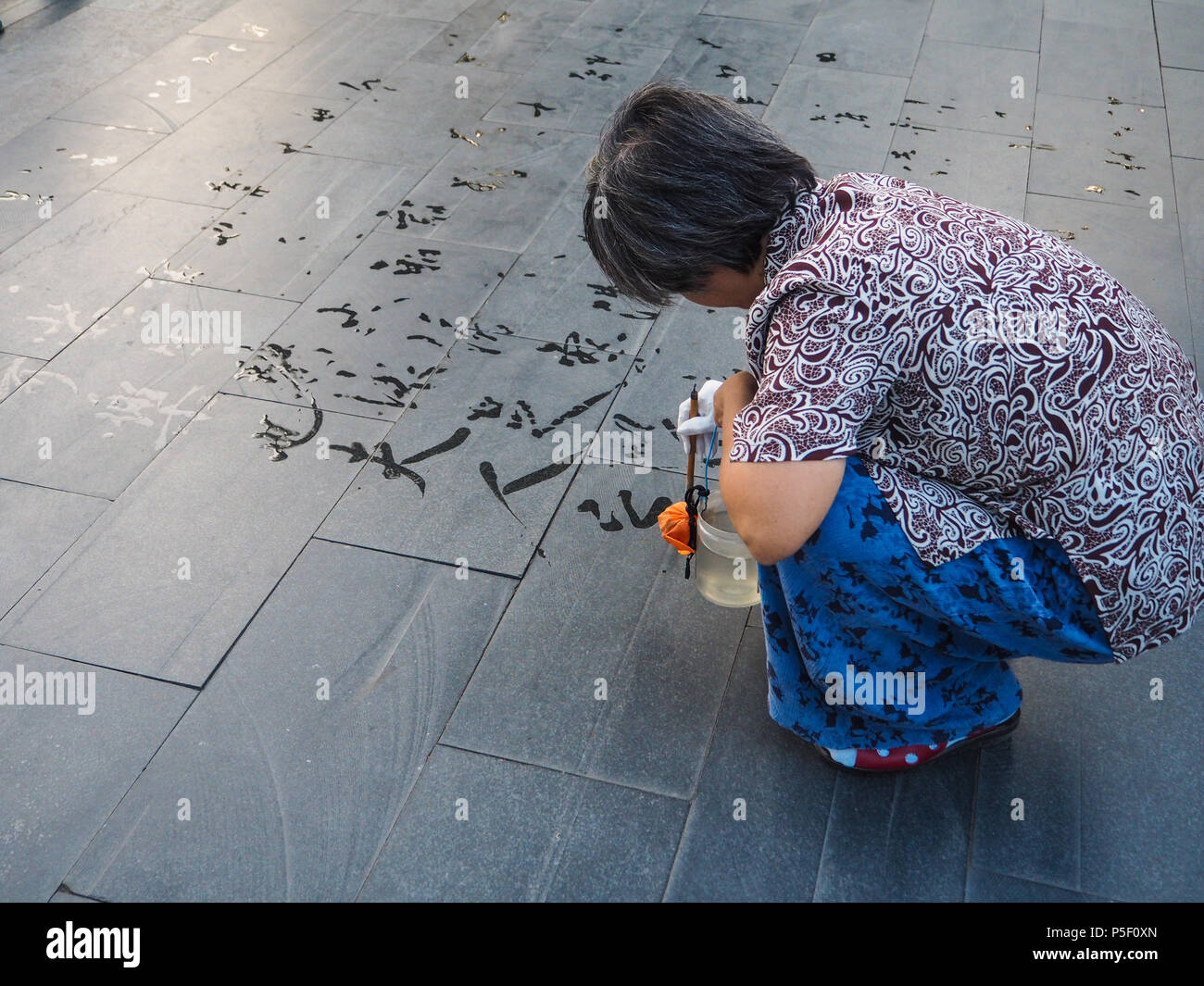 Older woman practicing calligraphy and writing ' le ye fu ren' meaning chearful lady Ye, Beijing, China - Stock Image