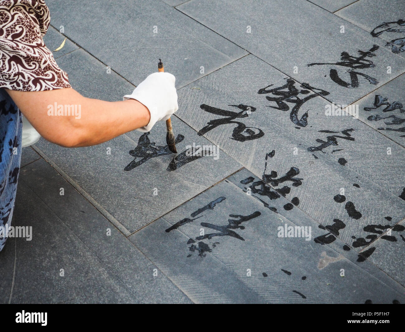 Older woman practicing calligraphy and writing ' Hui feng he chang' meaning a gentle and pleasant breeze,  Beijing, China - Stock Image