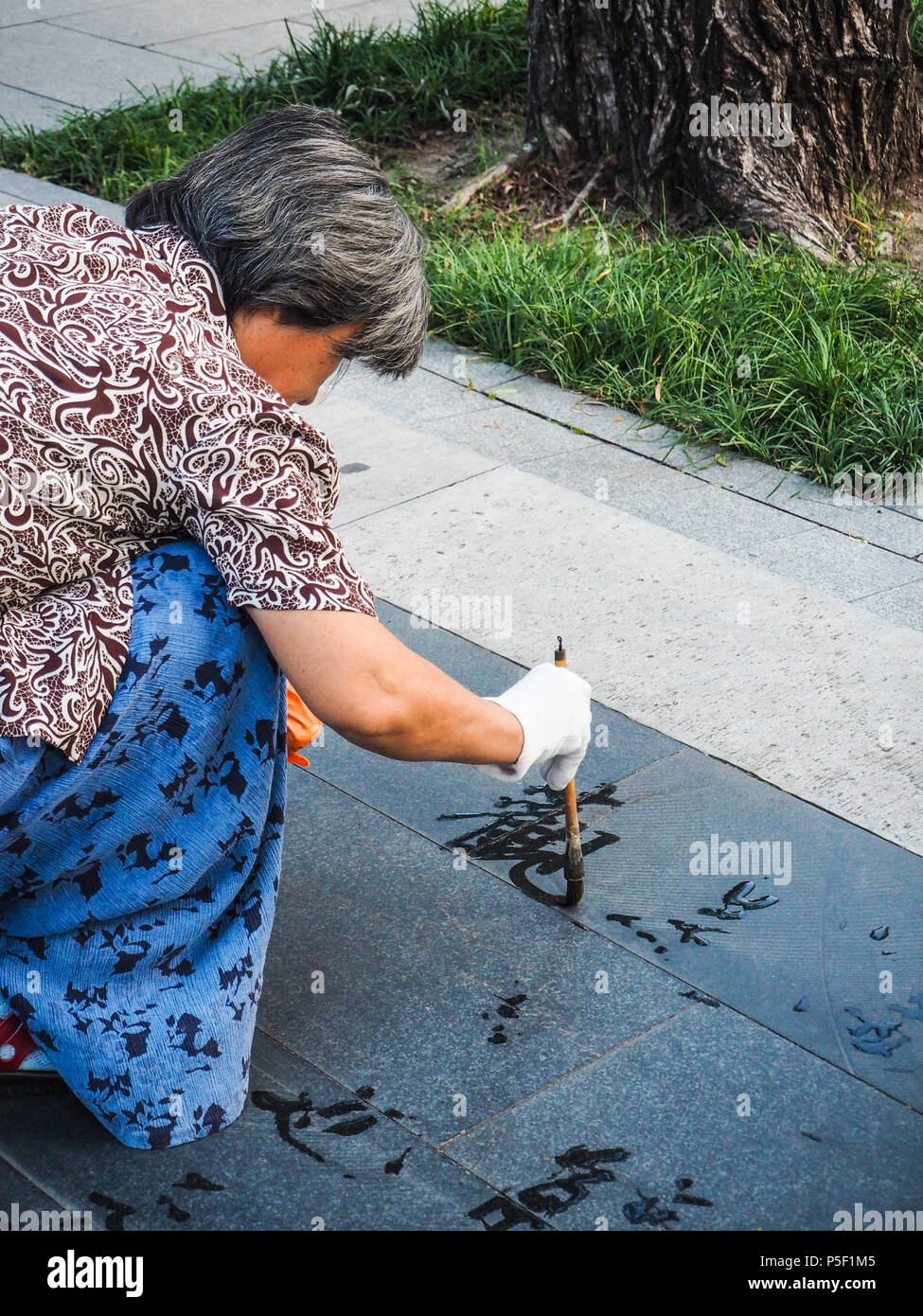 Beijing, China - September 2017: Older woman practicing water calligraphy but due to the heat the Chinese characters vanish instantly and are not read - Stock Image