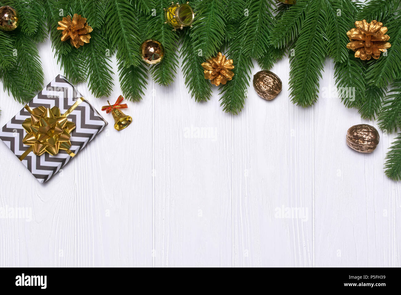 new years border on a white wooden background golden cones a gift a bell a drum christmas decor