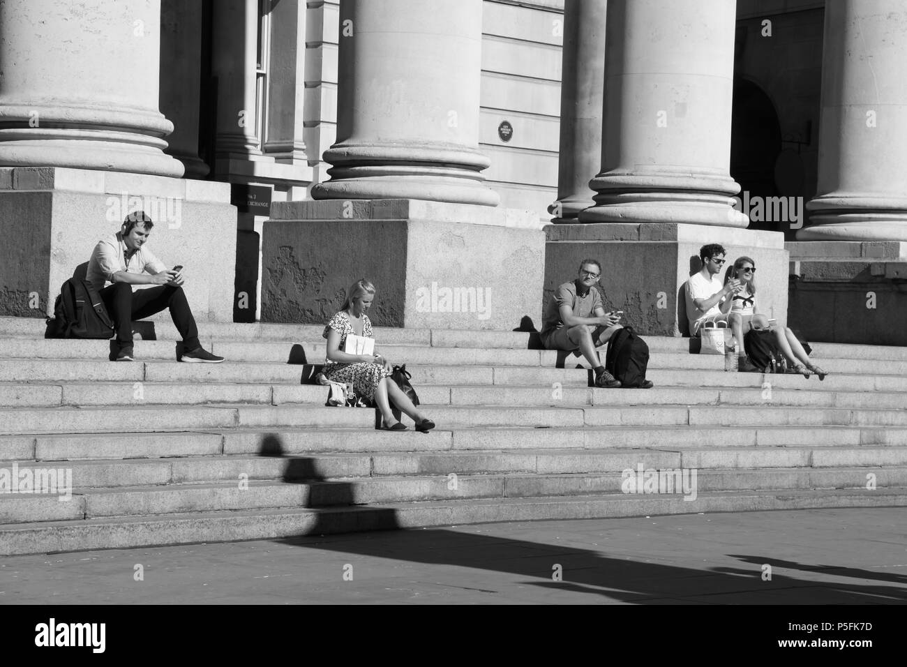 Office workers relaxing on the steps of The Royal Exchange (a luxury shopping centre above Bank station), London, England, UK, PETER GRANT - Stock Image