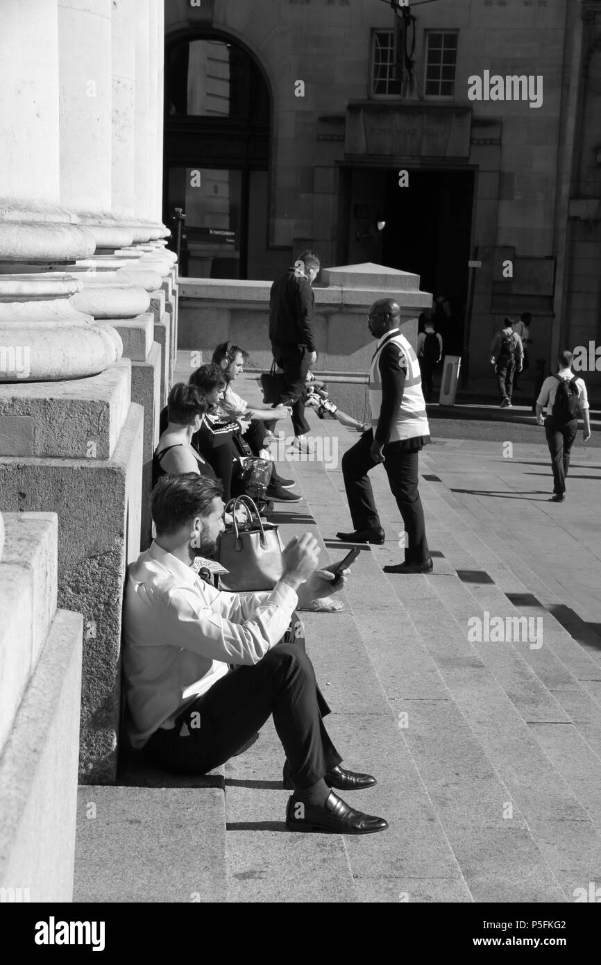 Office workers relaxing on the steps of the royal exchange a luxury shopping centre above