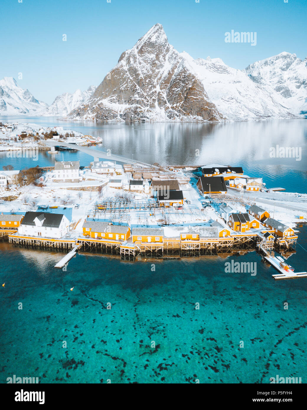 Aerial view of Lofoten winter scenery with traditional fisherman Rorbuer cabins and mountain peaks at sunrise, Sakrisoy, village of Reine, Norway - Stock Image