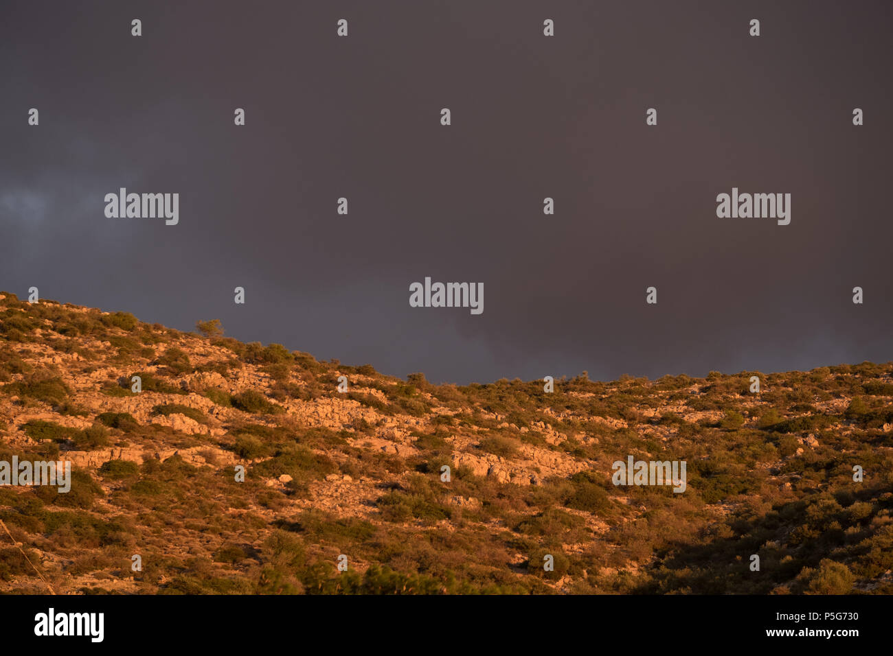 Greek mountain, Golden Hour Beautiful Light with Grey Dramatic Clouds, Saronida, Greece. Stock Photo