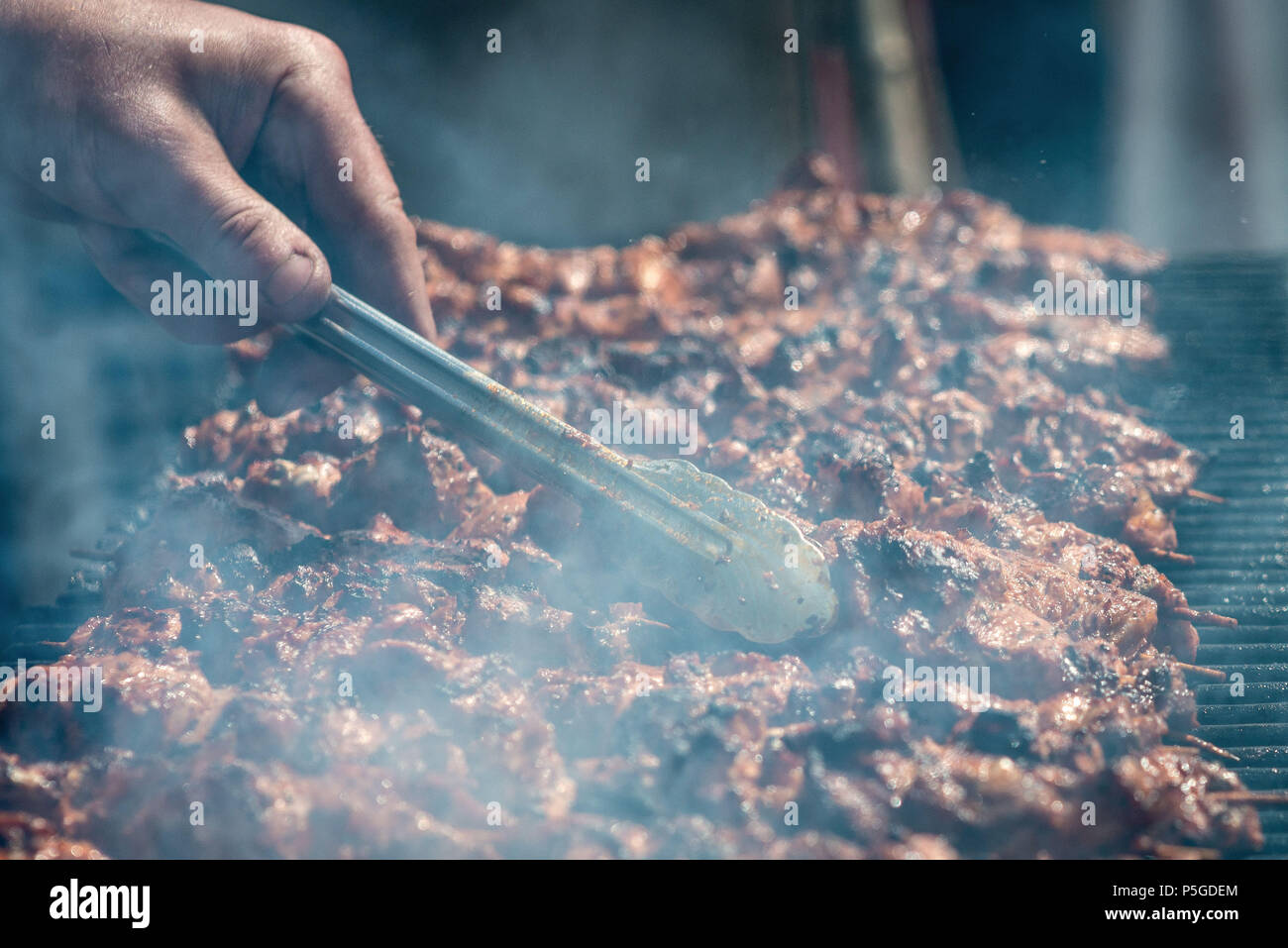 Meat on skewers fried on the grill in the open air, visible hands of the cook. Stock Photo