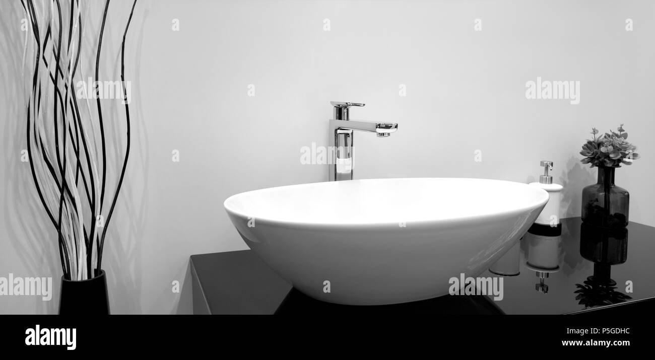 Luxury modern style faucet mixer on a white sink in a beautiful gray ...