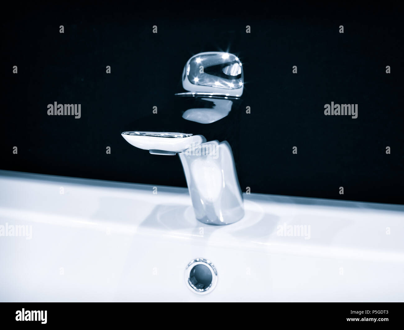 Luxury modern style faucet mixer on a white round sink in beautiful ...
