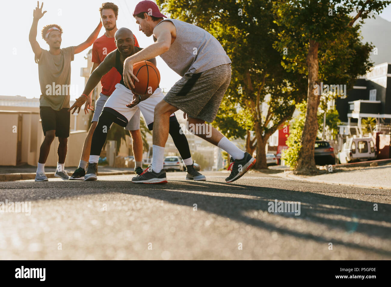 Men playing basketball game on a sunny day on an empty street. Men practicing basketball dribbling skills on street. Stock Photo