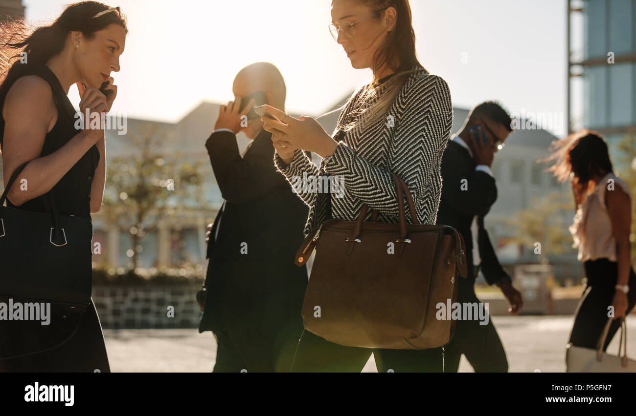 Men and women using mobile phone while commuting to office on a crowded street with sun flare in the background. Businessmen and businesswomen leading - Stock Image