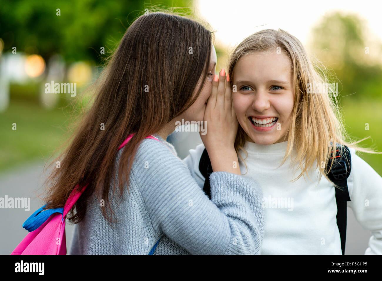 In summer city park. Two girl friends schoolgirls teenagers. Concept of joke, secret, fantasy, conversation, whisper, surprise. Emotion of happiness is pleasure, joy, smile, pleasure.After school. - Stock Image