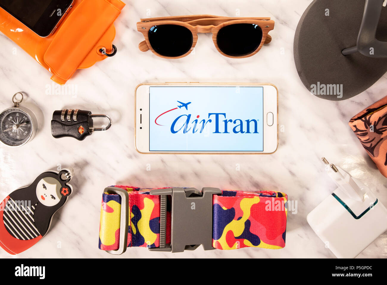 American low-cost AirTran Airways airline logo displayed on a smartphone screen next to travel accessories. Stock Photo