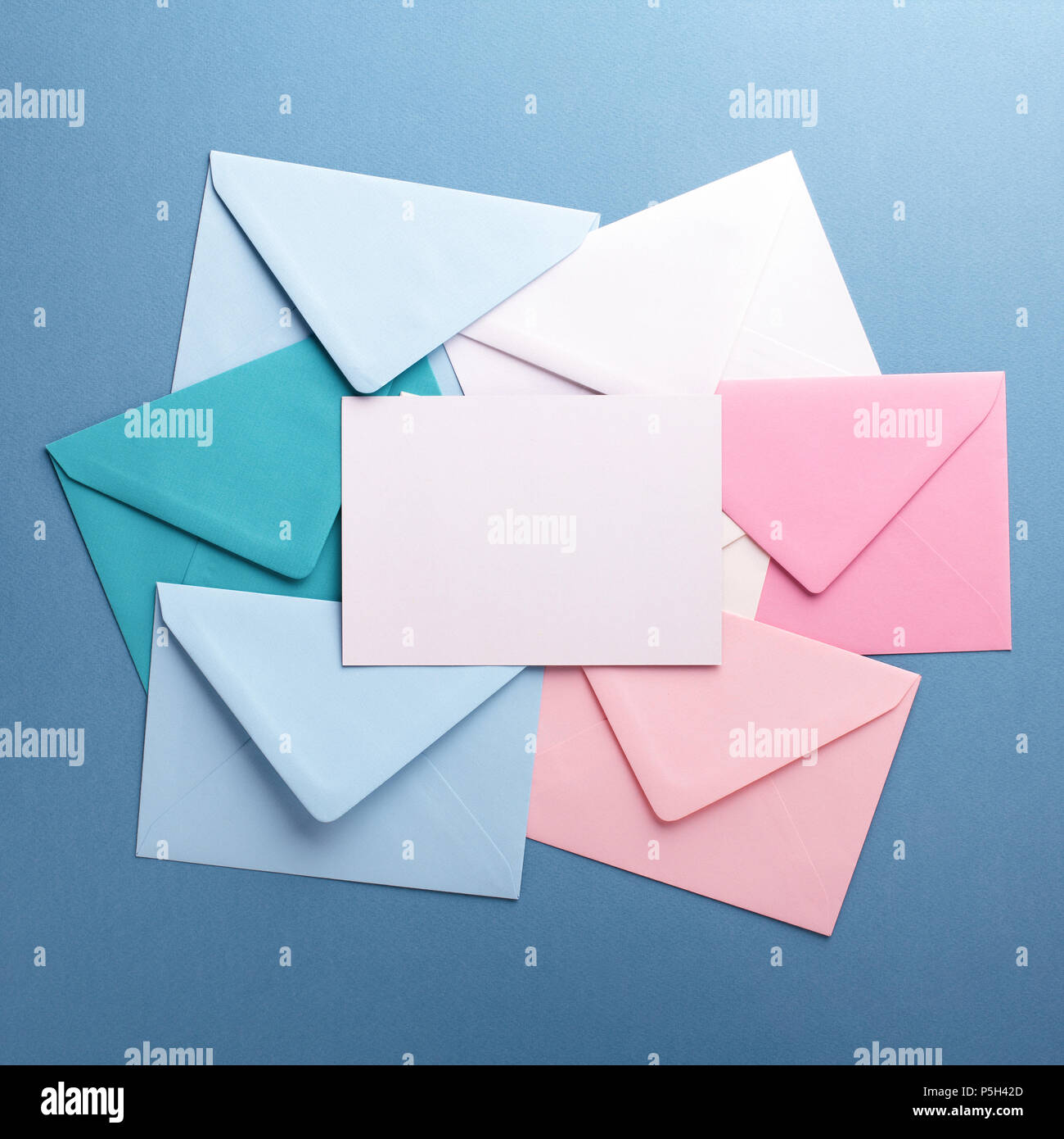 Group of colorful envelopes on grey table with empty card. Correspondence concept. Mockup. - Stock Image