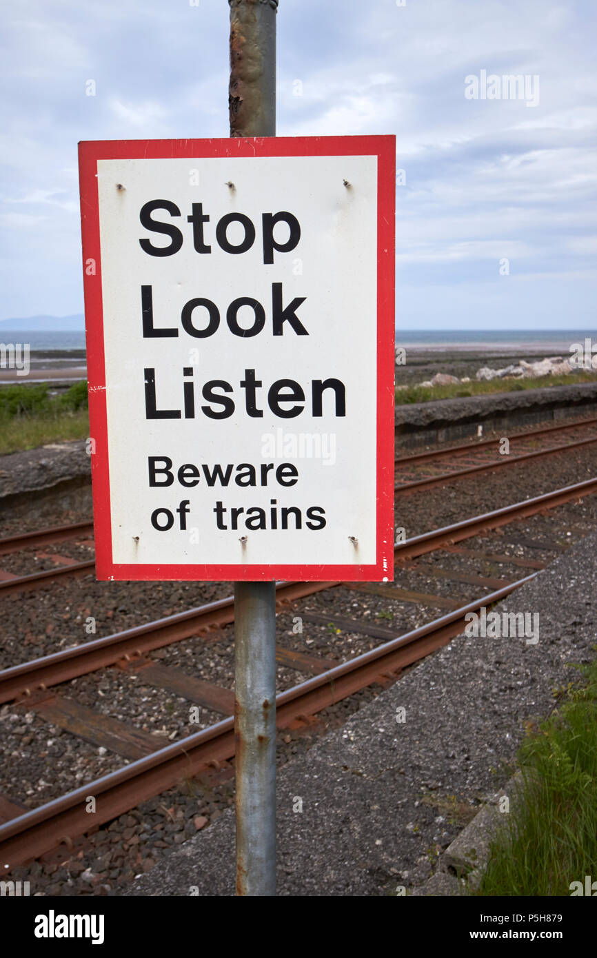 stop look listen warning sign at unmanned pedestrian level crossing on coastal train track Cumbria England UK - Stock Image