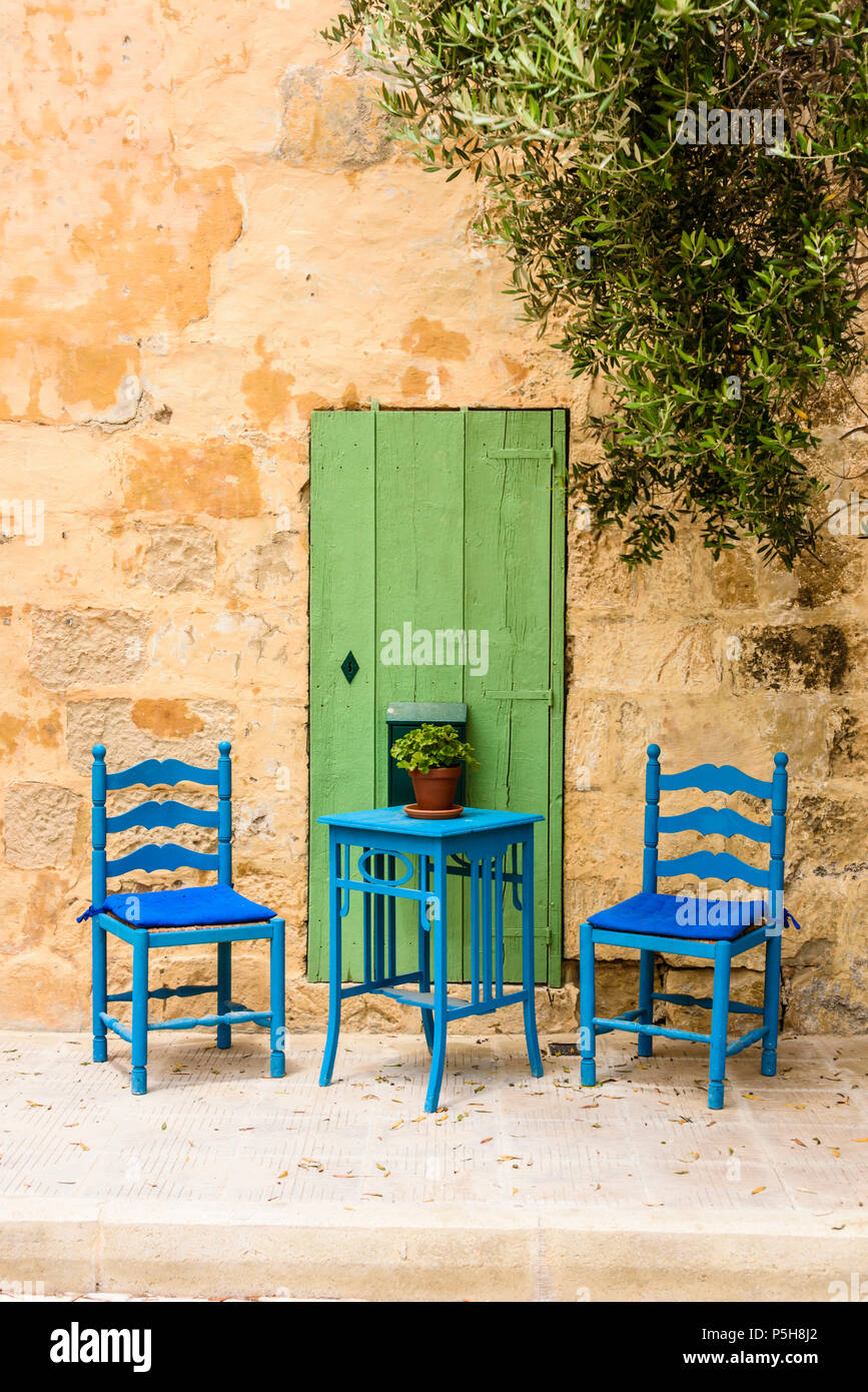 A pretty blue table and two chairs on the footpath in Gasri, Gozo, Malta. - Stock Image