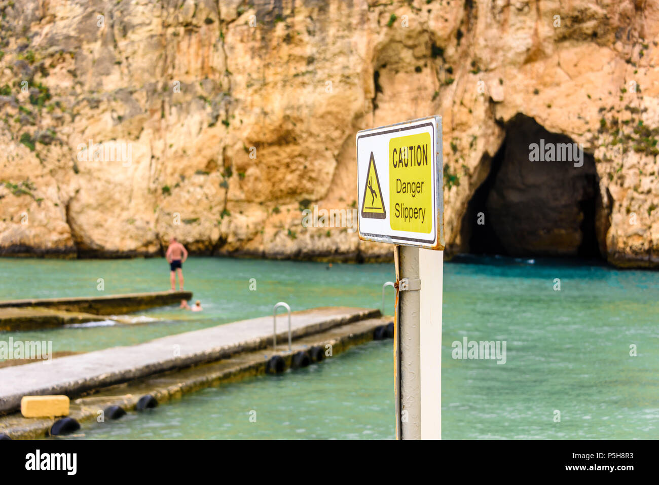 Sign at Dwerja, the inland sea, Gozo, Malta, warning that the jetties can be slippery.  The cave joins with the Mediterranean sea on the other side of - Stock Image