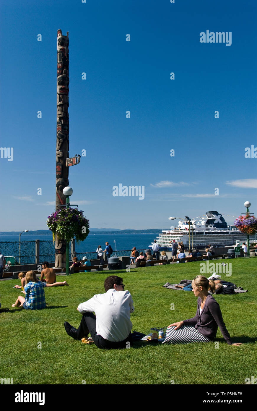 People enjoy a sunny day at Victor Steinbrueck Park, near Pike Place Market, in downtown Seattle, Washington. - Stock Image
