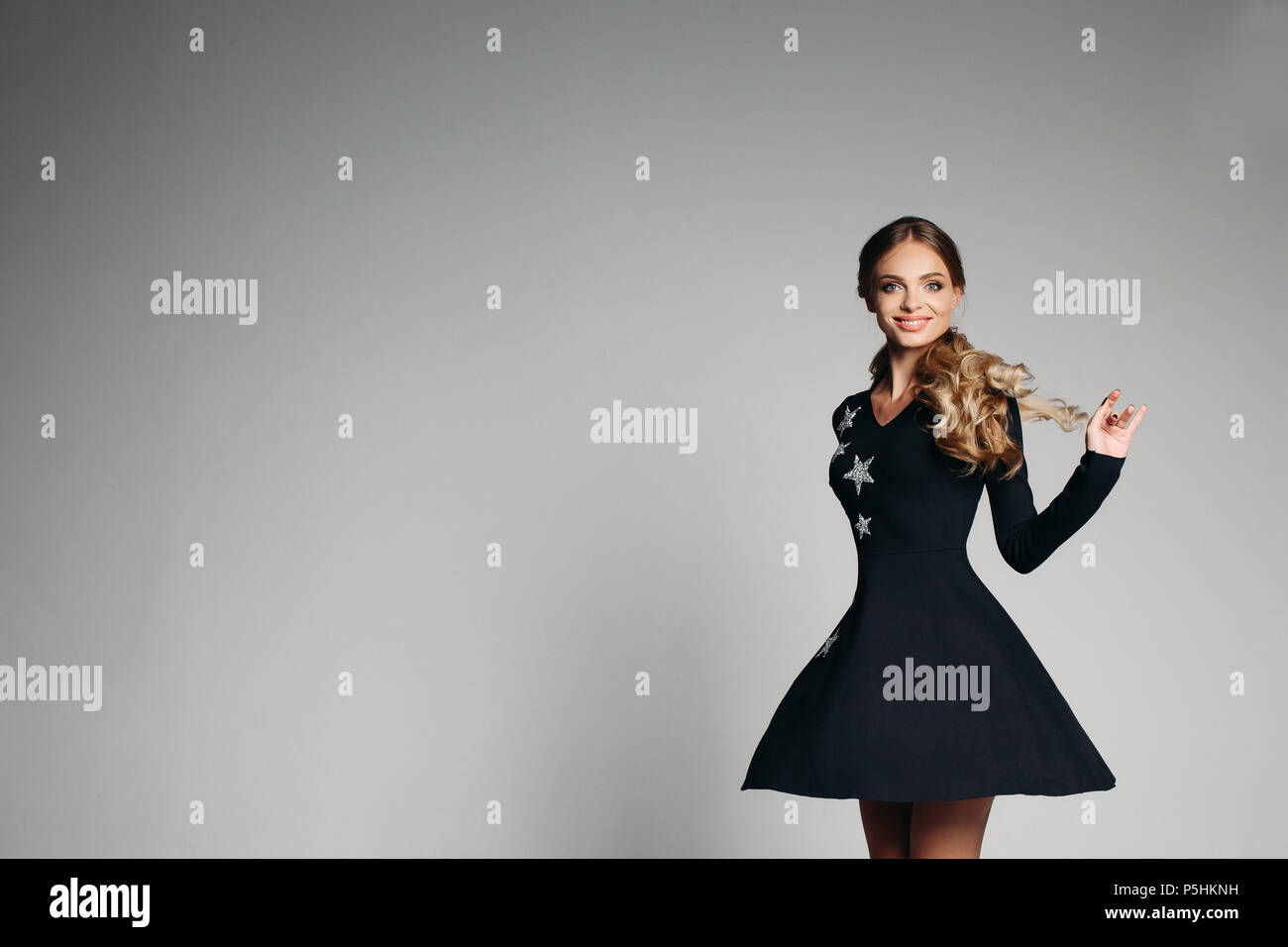 Gorgeous blonde girl with curly hair in black mini dress with silver stars. - Stock Image