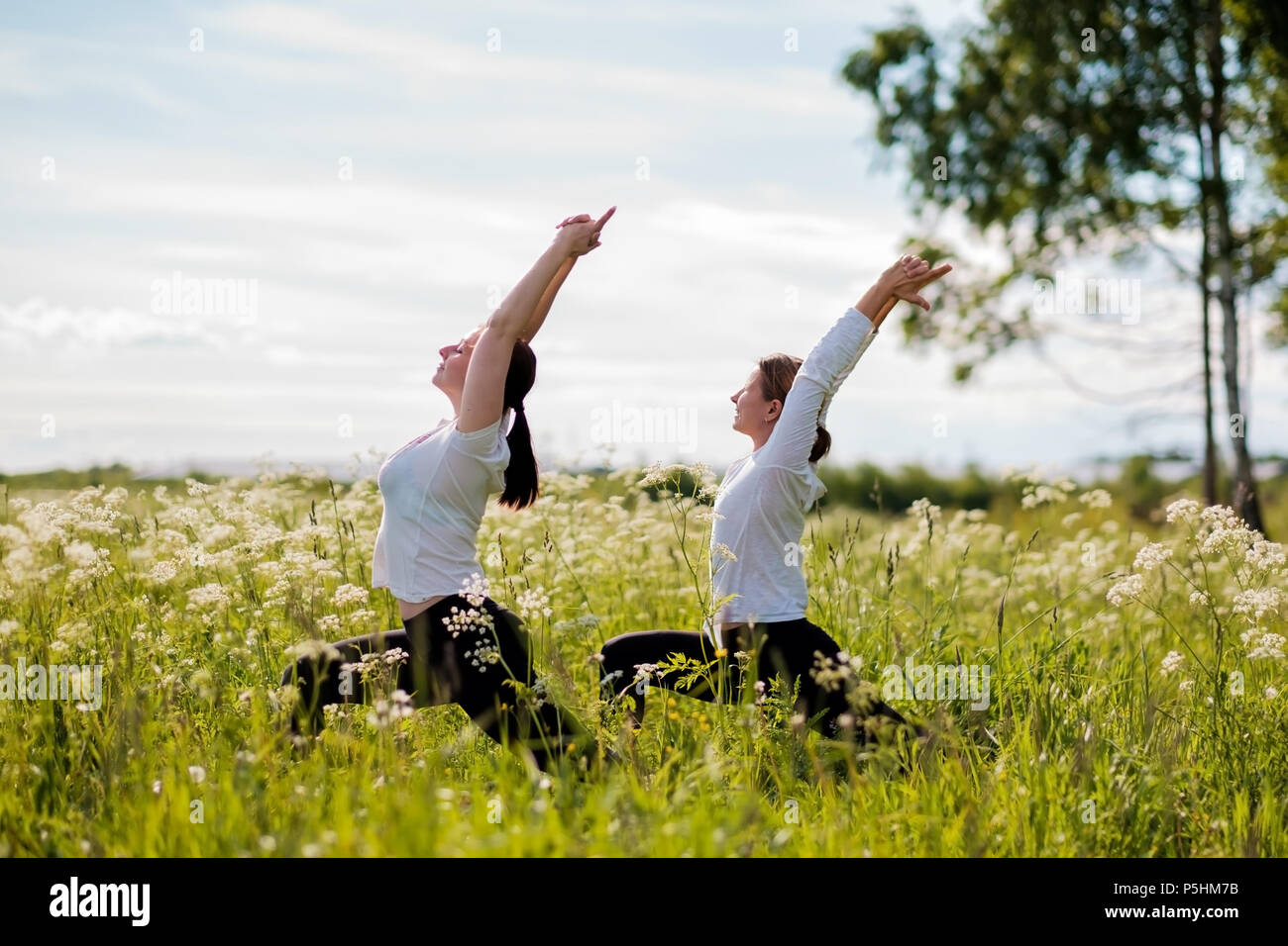 Young two women practicing yoga outdoor in park. - Stock Image