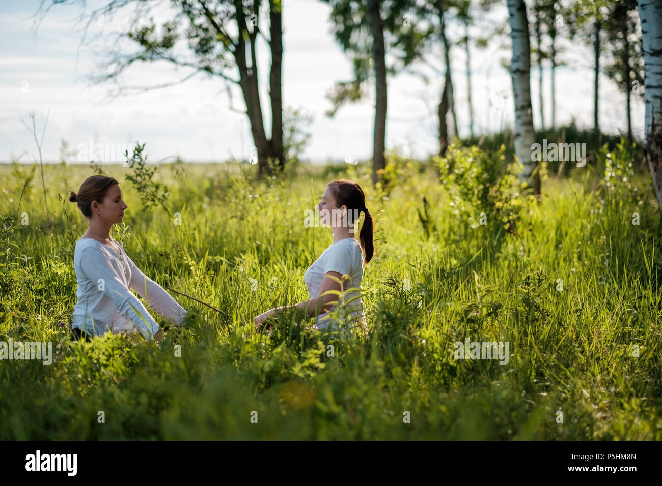 Portrait of two young woman enjoying pranayama or breathing exercises, relaxing, feeling alive and dreaming - Stock Image