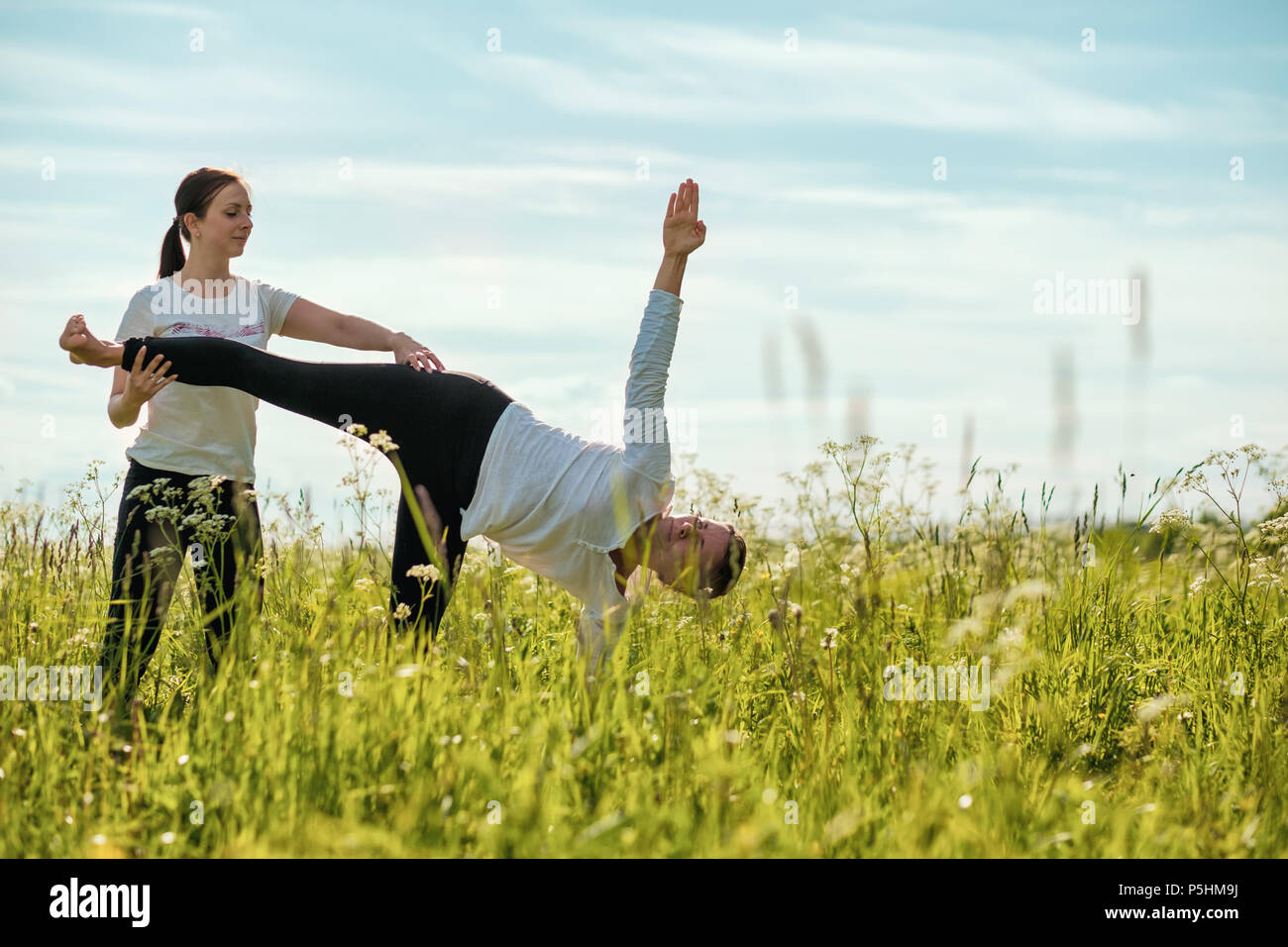 Sporty beautiful young woman practicing yoga, standing in Half Moon exercise, Ardha Chandrasana pose - Stock Image