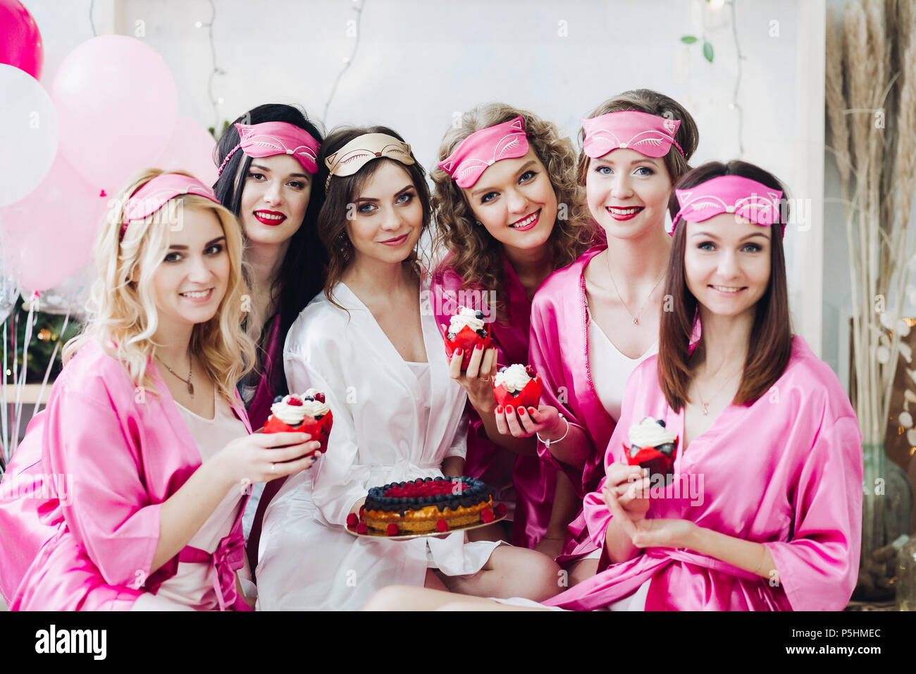Pretty Girls In Pink Robes And Sleep Masks With Desserts At Bridal Showers Stock Photo Alamy