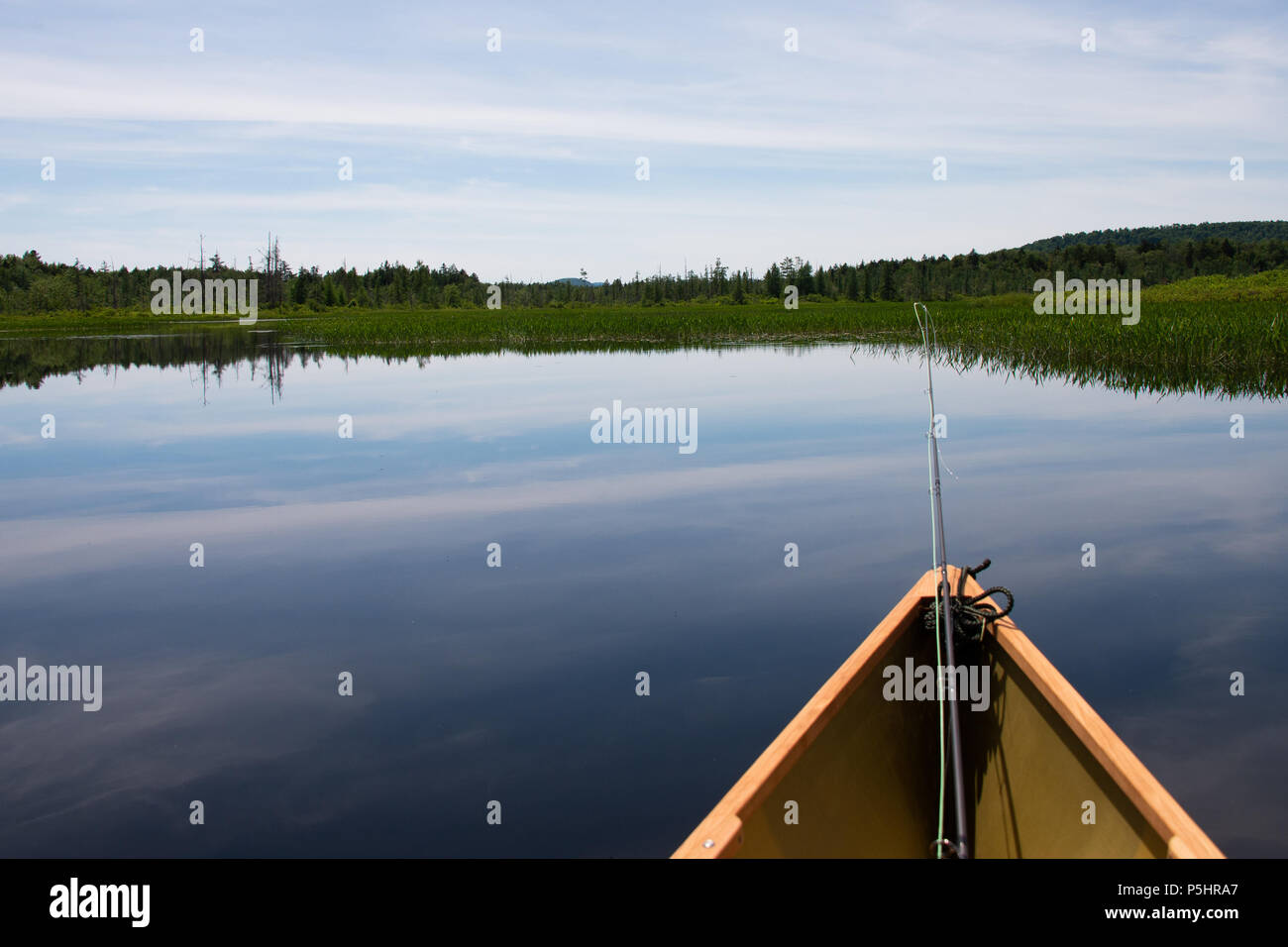A lightweight Kevlar canoe with a fly fishing rod floating on Kunjamuk Bay on the Sacandaga River in the Adirondack Mountains, NY USA. - Stock Image