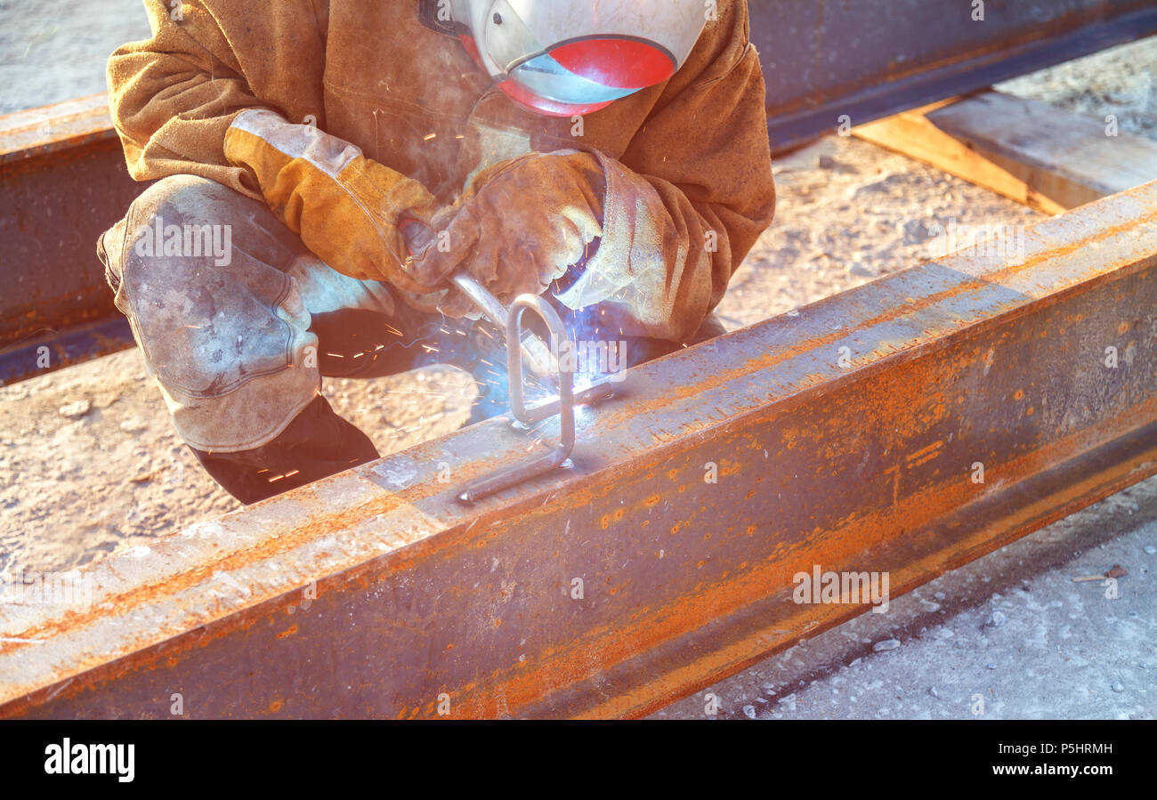 Worker at the enterprise welds a welded metal structure - Stock Image