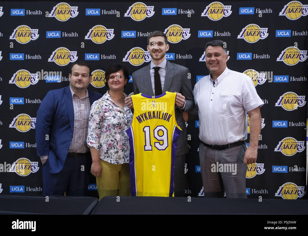 fb8a3a3325e Los Angeles Lakers rookie Sviatoslav Mykhailiuk holding his new jersey,  poses with his family at an introductory press conference in Los Angeles,  Tuesday, ...