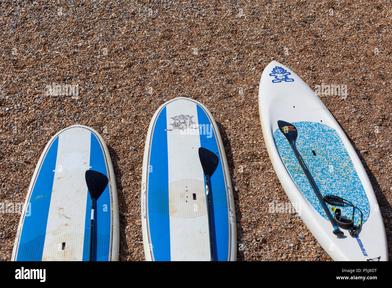 Hastings, East Sussex, UK. 27th Jun, 2018. UK Weather: The Hot and sunny weather continues in Hastings, East Sussex with highs of 30°C in some parts of the country. The heatwave that is hitting Britain is expected to last well into next week. Three paddle boards left on the beach. Photo Credit: PAL Images / Alamy Live News - Stock Image