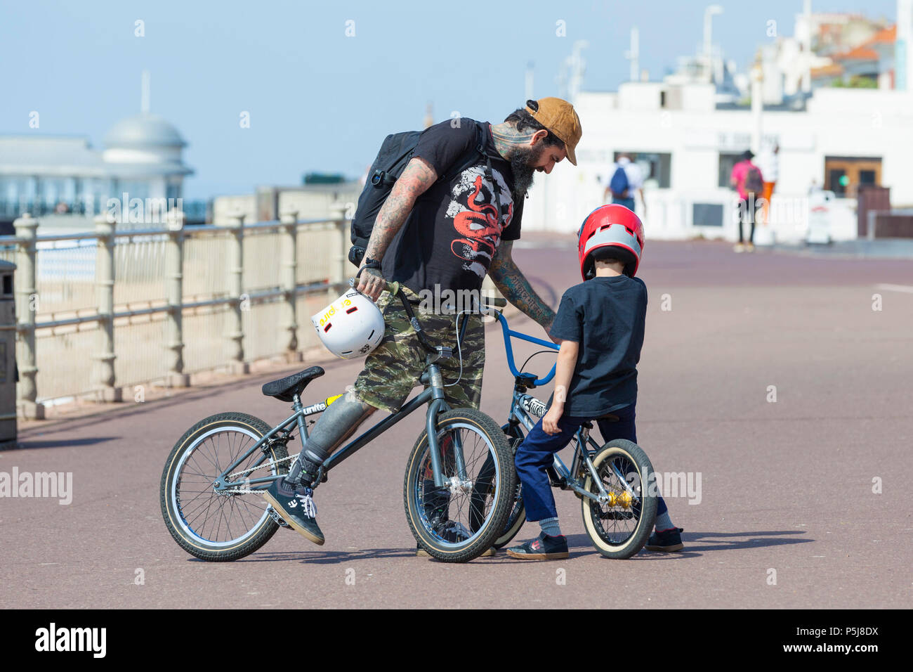 Hastings, East Sussex, UK. 27th Jun, 2018. UK Weather: The Hot and sunny weather continues in Hastings, East Sussex with highs of 30°C in some parts of the country. The heatwave that is hitting Britain is expected to last well into next week. Two bmx riders adjust their bikes. Photo Credit: PAL Images / Alamy Live News - Stock Image