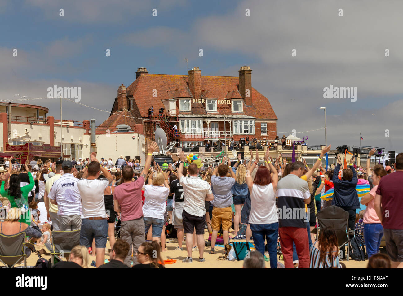 Gorleston, Norfolk, UK. June 27, 2018: Crowds of locals wave during filming of Danny Boyle's latest work, that imagines what might have happened if there hadn't been The Beatles. About 6,000 locals turned out as 'extras', organisers said. Credit: Paul Cowan/Alamy Live News - Stock Image