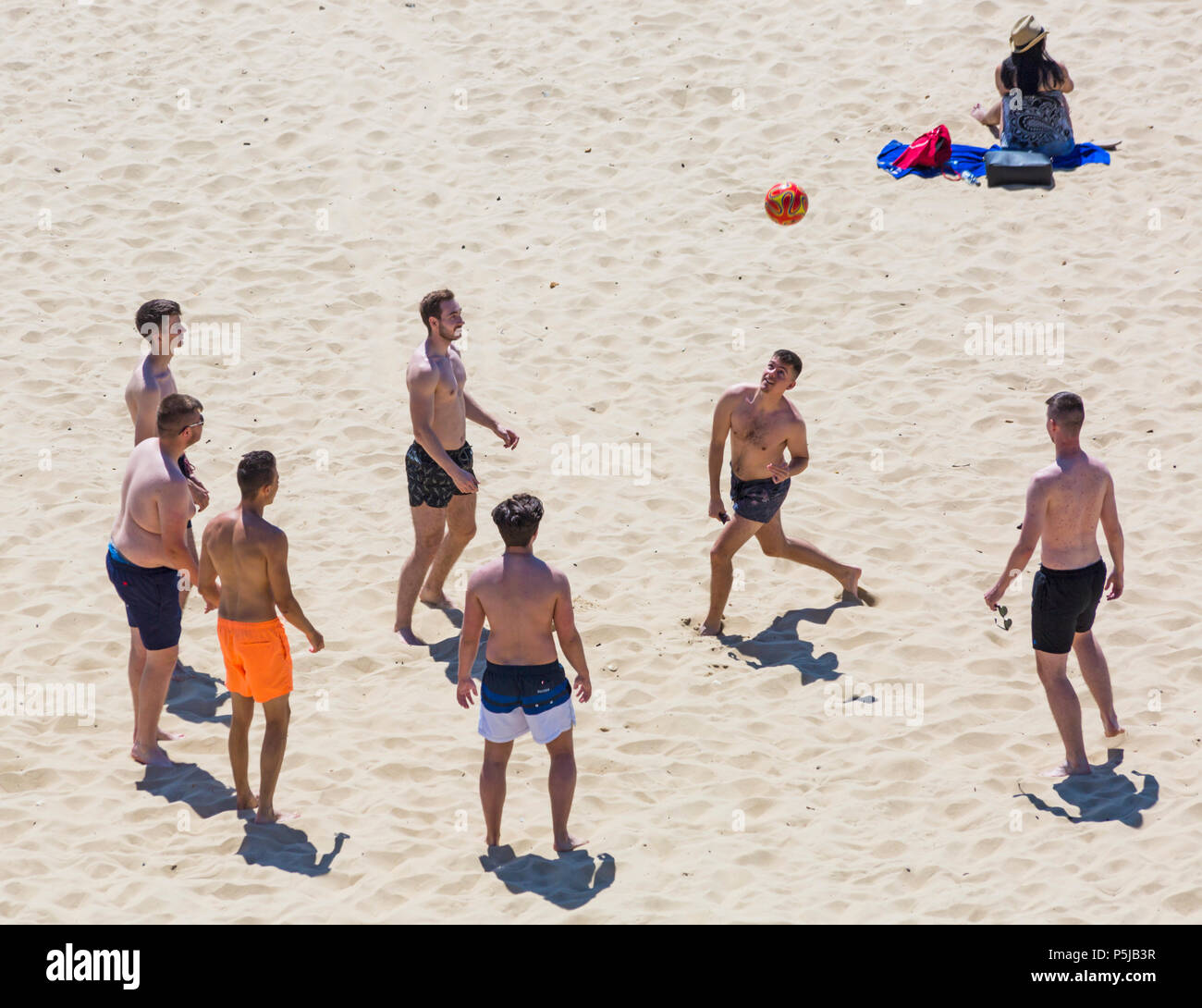 Bournemouth, Dorset, UK. 27th June 2018. UK weather: sunseekers head to the beaches at Bournemouth on another lovely warm sunny day with unbroken blue skies and sunshine. A nice cooling breeze today makes the heat more bearable. Footie on the beach. - Stock Image