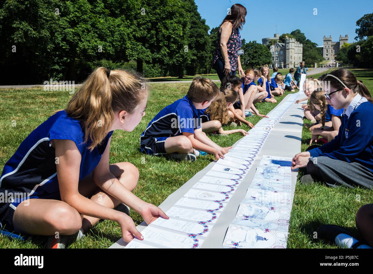 Windsor, UK. 27th June 2018. Local schoolchildren sit by the Long Walk in Windsor Great Park in front of Windsor Castle alongside a card prepared as a gift for the royal wedding of the Duke and Duchess of Sussex in a Guinness World Records™ record attempt for the title of the Longest Concertina Folded card by the Busy Buttons Design Centre CIC and a wide cross-section of the local community. The card has been signed by 4797 people and has an as yet unconfirmed length of 1367 metres. Credit: Mark Kerrison/Alamy Live News - Stock Image