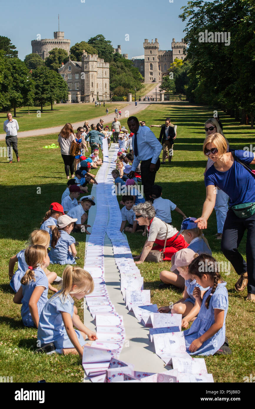 Windsor, UK. 27th June 2018. Local schoolchildren on the Long Walk in front of Windsor Castle help to display a card prepared as a gift for the royal wedding of the Duke and Duchess of Sussex in a Guinness World Records™ record attempt for the title of the Longest Concertina Folded card by the Busy Buttons Design Centre CIC and a wide cross-section of the local community. The card has been signed by 4797 people and has an as yet unconfirmed length of 1367 metres. Credit: Mark Kerrison/Alamy Live News - Stock Image
