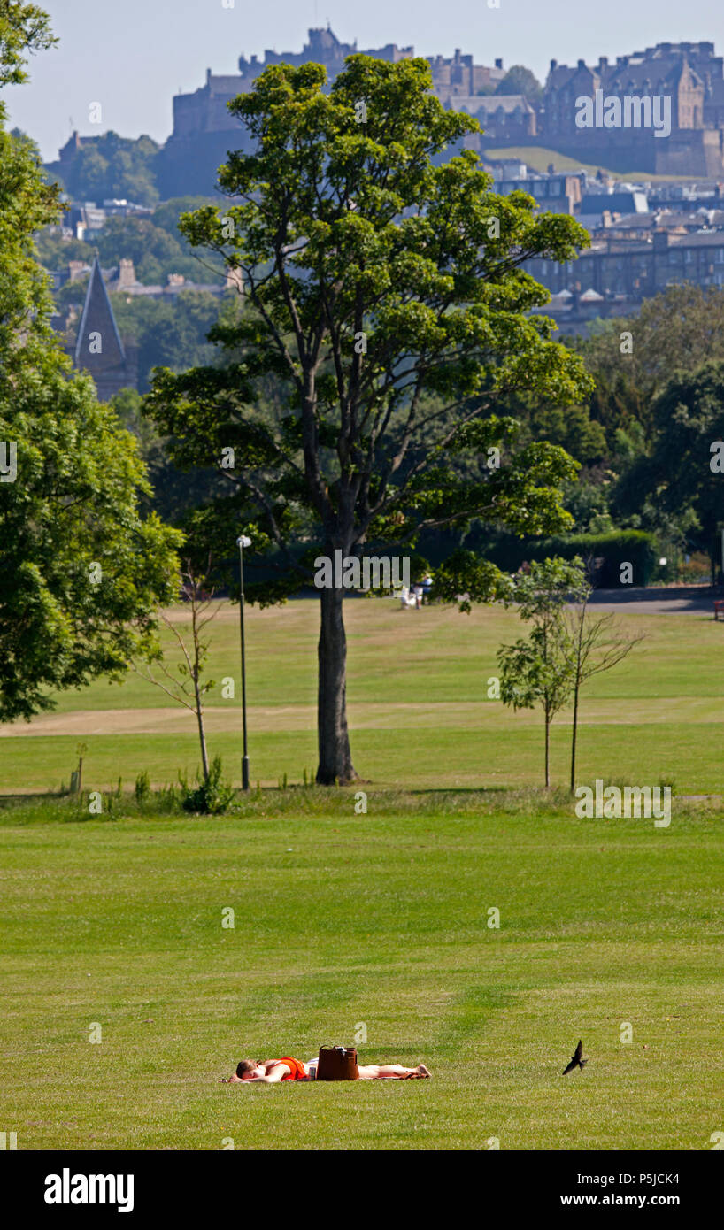 Scotland, 27 June 2018, unlike other areas the sun eventually showed up in Edinburgh around mid-morning after a very misty start with coastal haar, one female sunbather enjoys the 17 degree heat in Inverleith Park with the castle in the background and a passing bird in the foreground. - Stock Image
