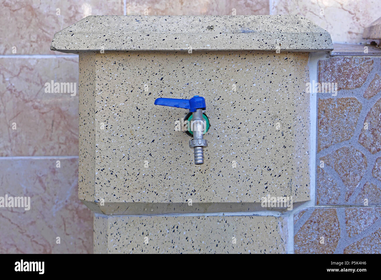 Water faucet with blue handle and hose attachment - Stock Image