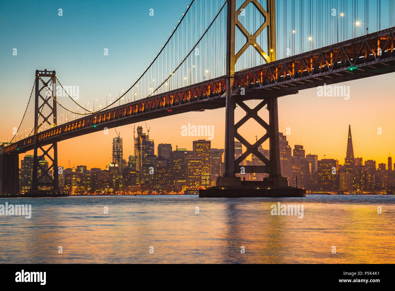 Classic panoramic view of San Francisco skyline with famous Oakland Bay Bridge illuminated in beautiful golden evening light at sunset in summer - Stock Image