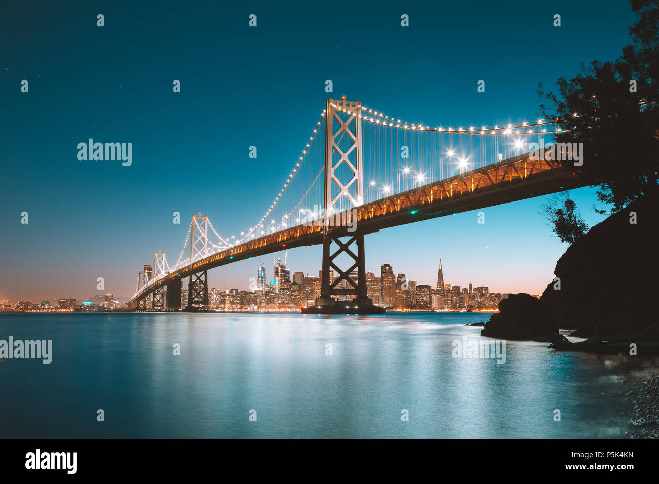 Classic panoramic view of San Francisco skyline with famous Oakland Bay Bridge illuminated in beautiful evening twilight at dusk in summer - Stock Image