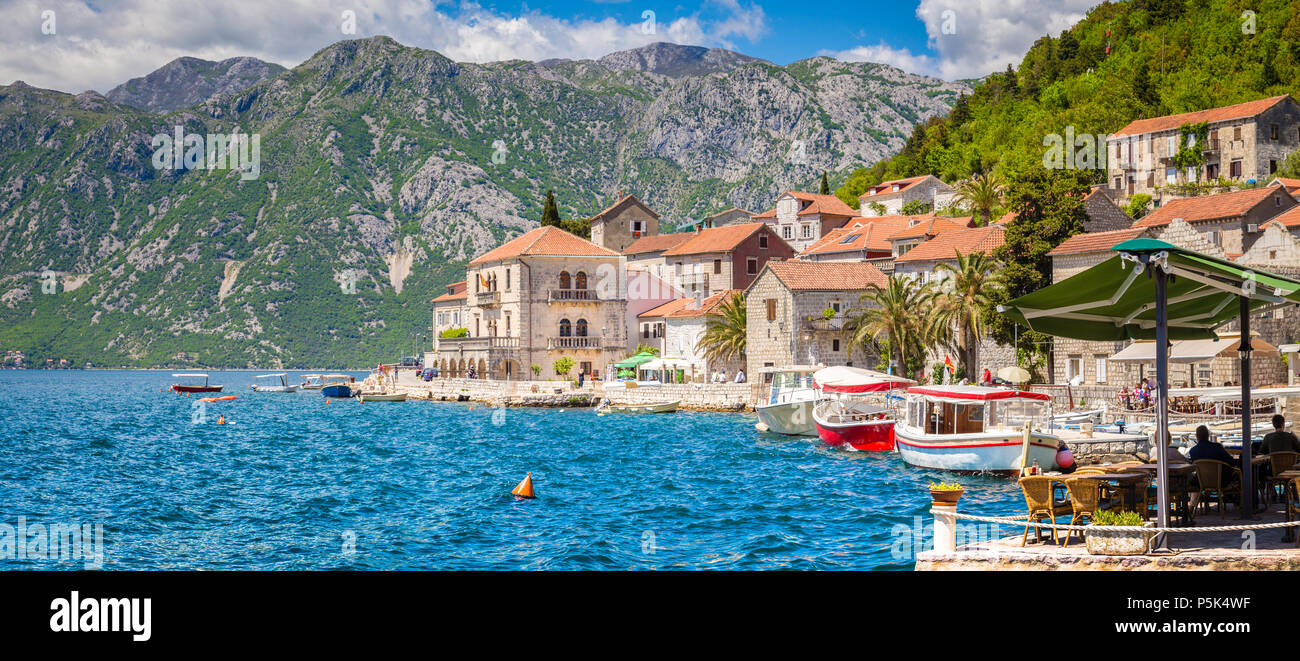 Scenic panorama view of the historic town of Perast at famous Bay of Kotor on a beautiful sunny day with blue sky and clouds in summer, Montenegro, so - Stock Image