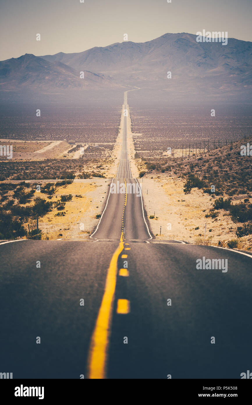 Classic panorama view of an endless straight road running through the barren scenery of the American Southwest with extreme heat haze on a beautiful s - Stock Image