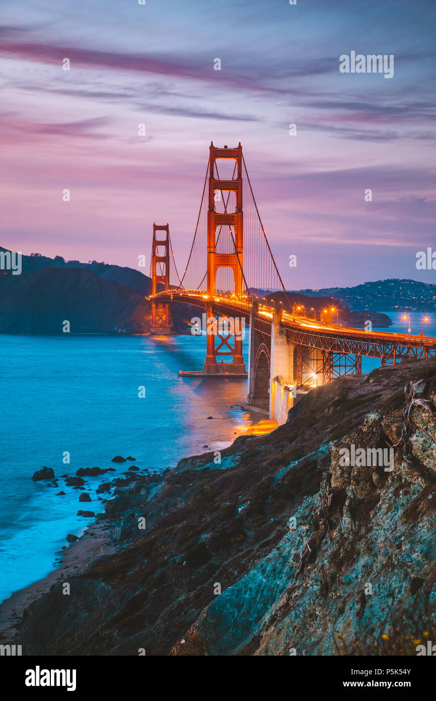 Classic panorama view of famous Golden Gate Bridge seen from scenic Baker Beach in beautiful post sunset twilight with blue sky and clouds at dusk in  - Stock Image