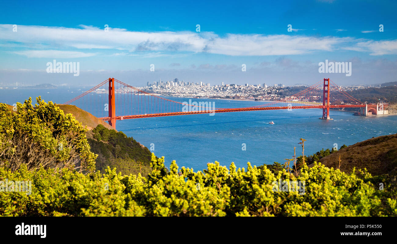 Classic aerial view of famous Golden Gate Bridge with the skyline of San Francisco in the background on a beautiful sunny day with blue sky and clouds - Stock Image
