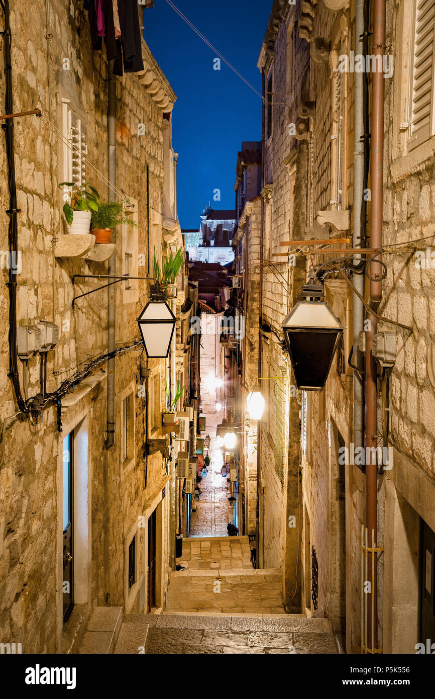 Classic vertical view of small alleyway in the old town of Dubrovnik, in beautiful morning twilight before sunrise at dawn in summer, Dalmatia, Croati - Stock Image