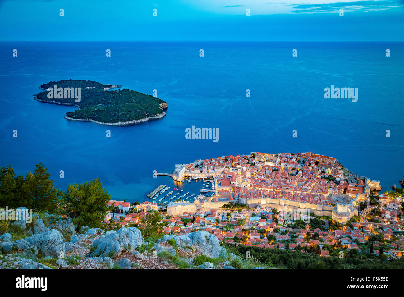 Panoramic aerial view of the historic town of Dubrovnik with Lokrum island in beautiful evening twilight at dusk, Dalmatia, Croatia - Stock Image