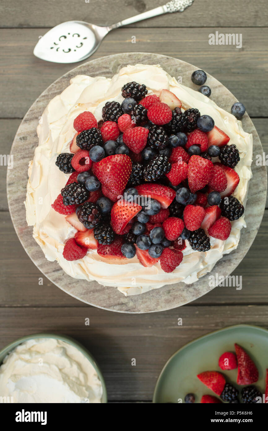 Pavlova meringue cake dessert made with strawberries, blackberries, raspberries and blueberries,  planted on a granite platform - Stock Image